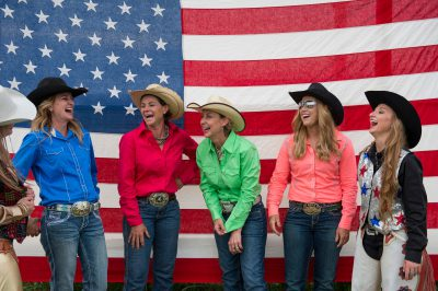 Photo: Rodeo queens laugh during a photo shoot in front of an American flag.