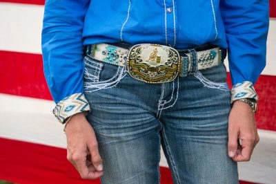 Photo: A close up of a rodeo queen's belt buckle in front of an American flag.
