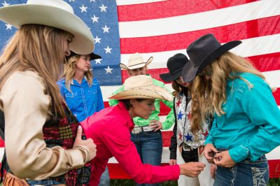 Photo: Rodeo queens in front of an American flag.