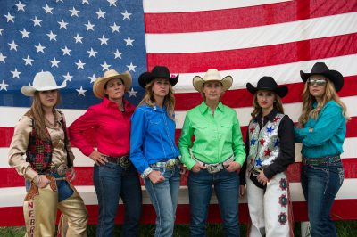 Photo: Rodeo queens pose for a portrait in front of an American flag.