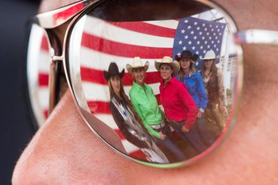 Photo: Sunglasses reflect an image of rodeo queens as they pose for a portrait in front of an American flag.