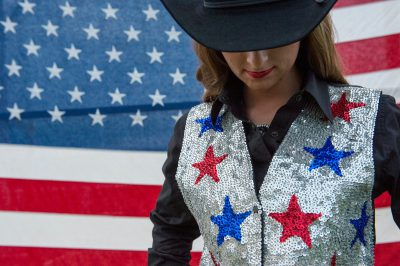 Photo: A rodeo queen poses for a portrait in front of an American flag.