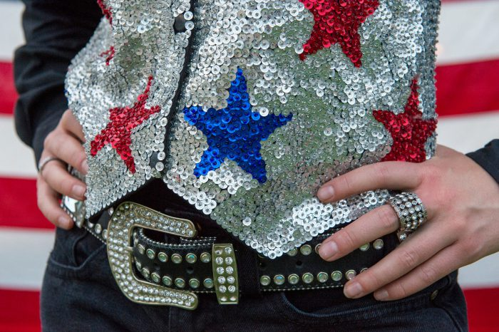 Photo: A close up of a rodeo queen's belt and sequined vest in front of an American flag.