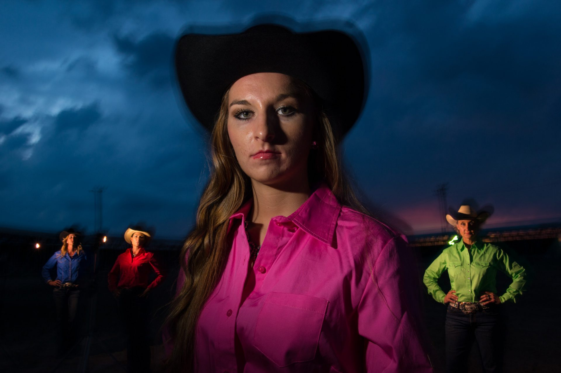 Photo: Rodeo queens pose for a portrait at night.