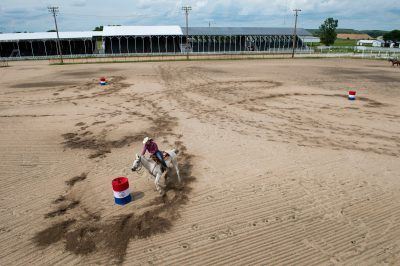 Photo: A teenage girl practices barrel racing with her horse.