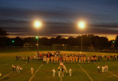 Photo: The crowd salutes the flag before a six-man football game in Chester, Nebraska.