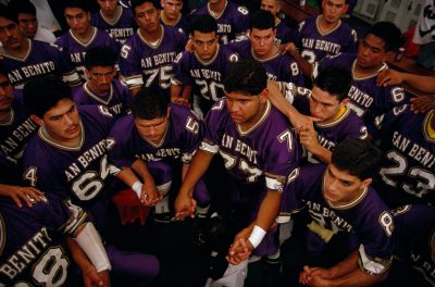Photo: San Benito high school greyhounds football team hold hands in prayer before an important game in San Benito, Texas.