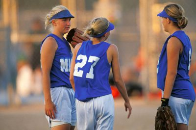 Photo: Teammates confer with one another at a softball game in Lincoln, Nebraska.