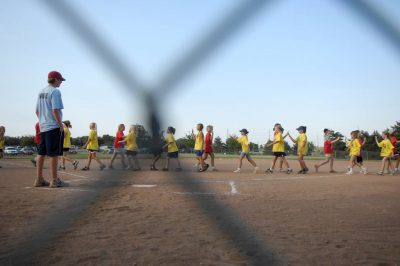 Photo: YMCA softball players high five their opponent after a game in Lincoln, Nebraska.