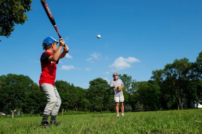 Photo: A father pitches a ball to his son at a baseball practice.