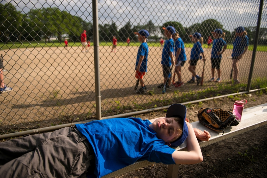 Photo: An elementary aged boy rests on the bleachers before his t-ball game.