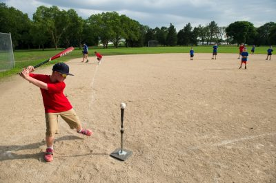 Photo: An elementary aged boy at bat during a t-ball game.
