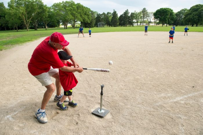 Photo: A coach helps an elementary aged boy bat during a t-ball game.