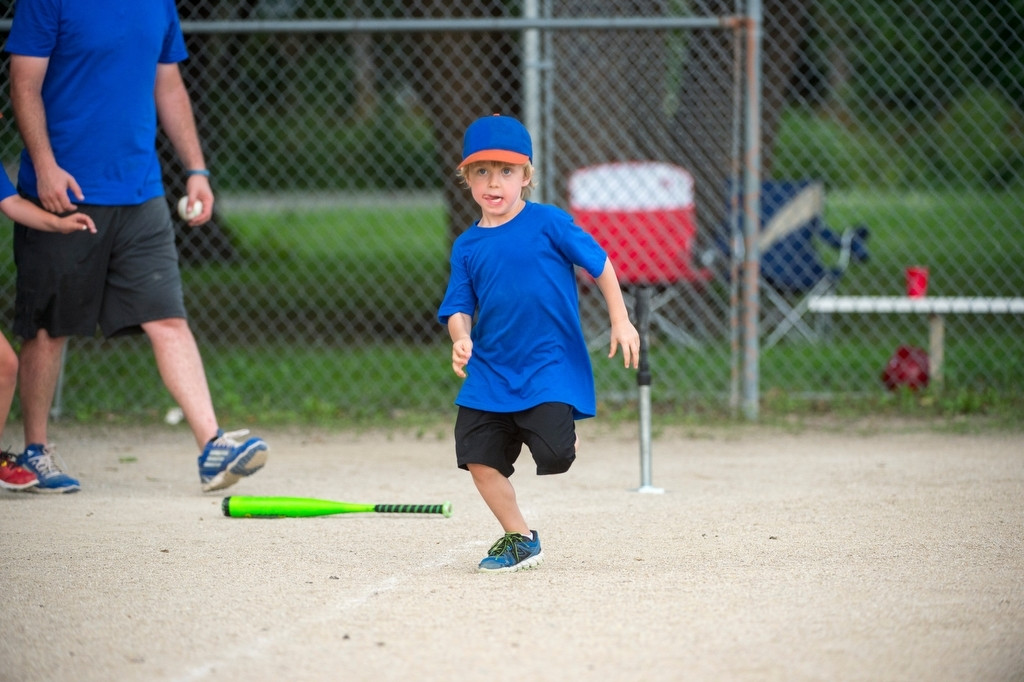 Photo: An elementary age boy runs to first base during a t-ball game.