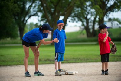 Photo: A t-ball coach encourages an elementary age boy standing on second base.