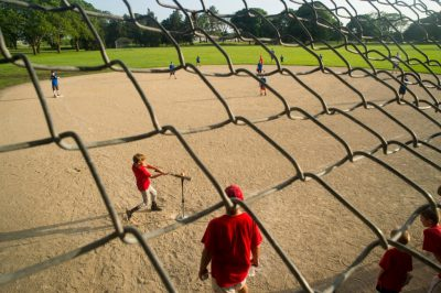 Photo: An elementary age boy steps up to the plate with his coach during a t-ball game.