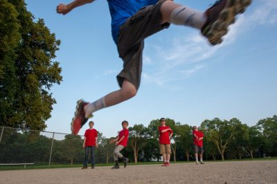 Photo: Elementary aged boys take turns running and jumping after their t-ball game.
