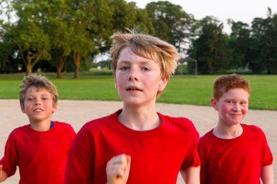 Photo: Three elementary aged boys run together on the t-ball field.