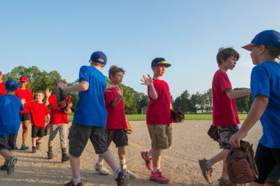 Photo: Two opposing teams of elementary aged boys show signs of good sportsmanship after their t-ball game.
