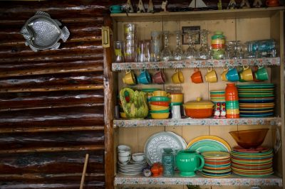 Photo: Colorful dishes sit on a shelf in a cabin.