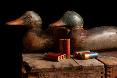 Photo: Antique duck decoys and shotgun shells sit on an old wooden crate.