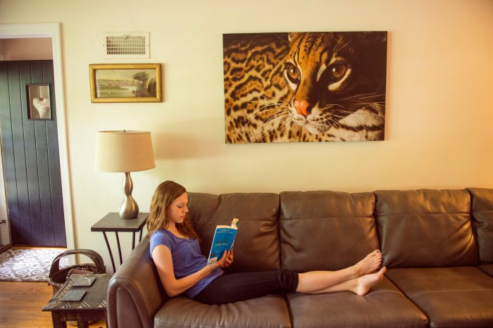 A canvas of an ocelot hangs in a living room.