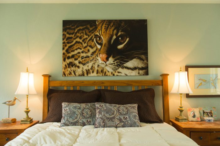 A canvas of an ocelot hangs in a bedroom.