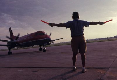 Photo: A landing crew member directs an airplane.