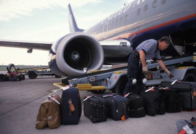 Photo: An airport worker loads lugguage onto the aircraft.