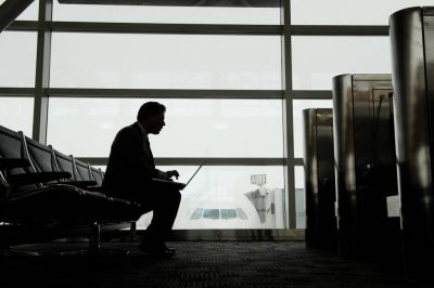 Photo: A silhouetted man on his computer while he waits for his airplane to baord.