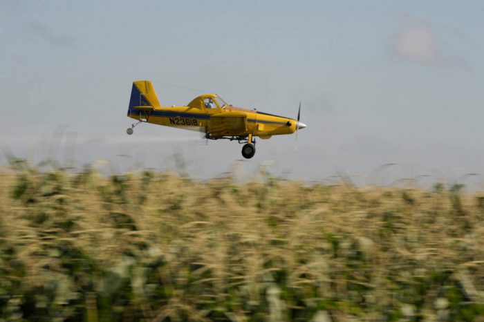 Photo: Crop dusting plane over corn in the Platte River Valley of central Nebraska.