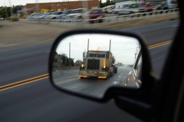 Photo: A semi trailer as seen through a car's rearview mirror.